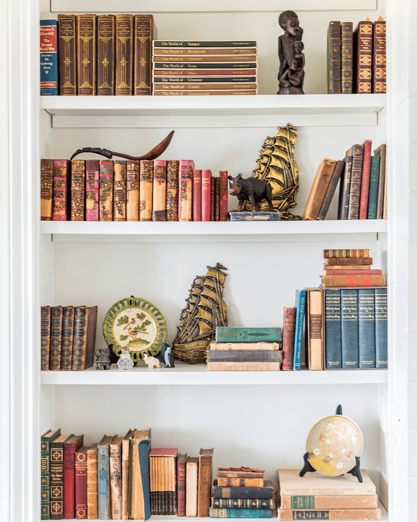White shelves filled with old books as well as decorative antiques.