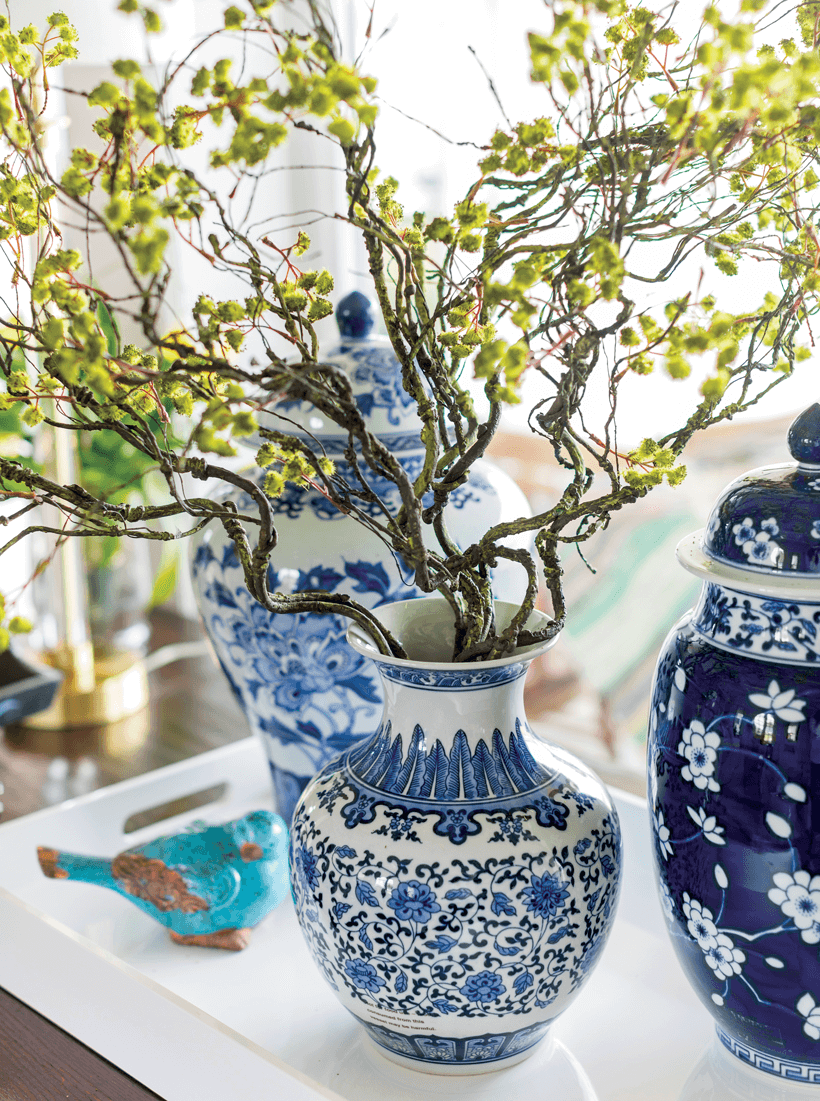 A white and blue vases with decorative tree branches in it.