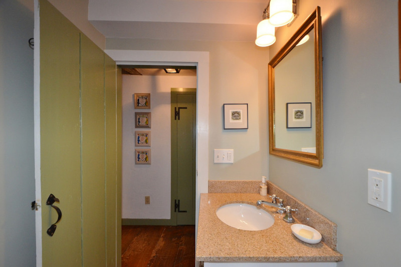 A bathroom with blue walls, one sink, and an old-fashioned green door.