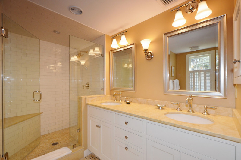 A bathroom with yellow walls and countertops and a glass shower.