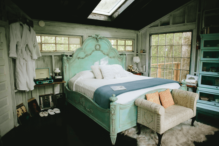 The antique turquoise bed makes the treehouse getaway a romantic place to stay