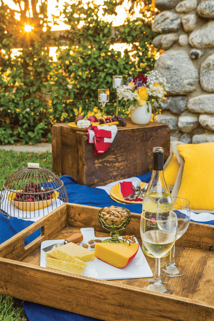 Outdoor picnic spread. Blanket covered in wine glasses, cheese and appetizers with sun setting in the background.