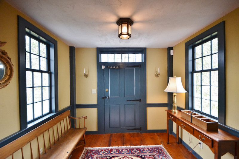 An entryway with light yellow walls and a blue door and window frames.