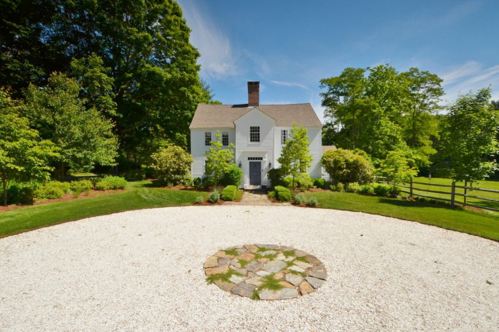 Historic white cottage set back on a circular driveway.