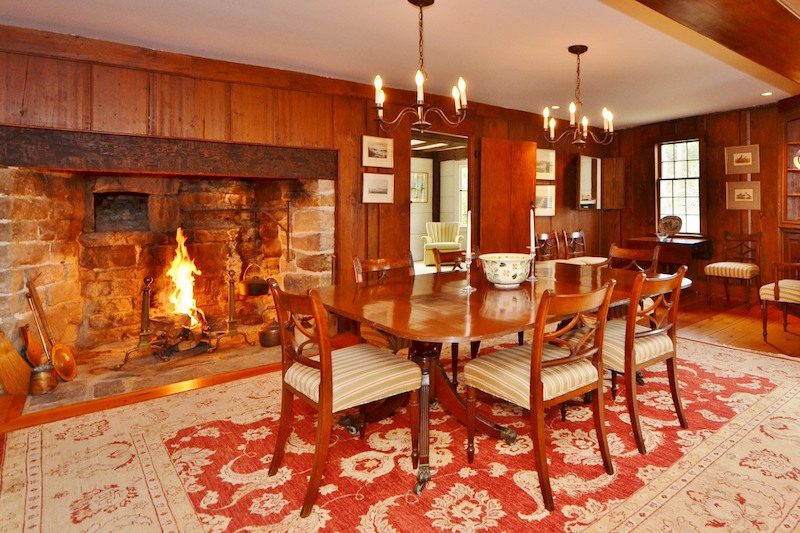 A dining room with a large rug and a large open fireplace lined with stone.