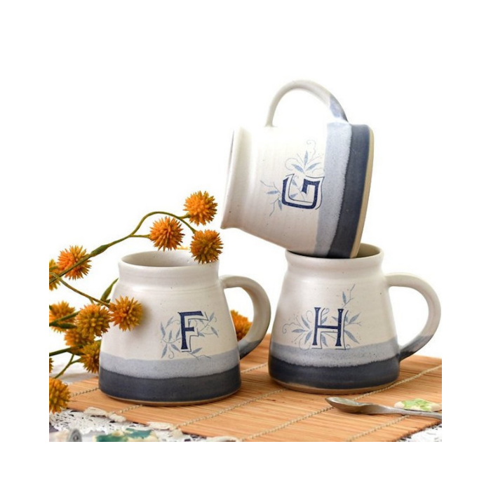 Stack of three mugs with blue detailing and monogram letter F, G and H on a table with yellow flowers