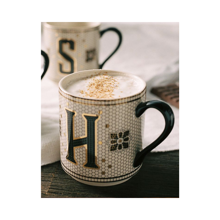 Mug with subway tile design, monogram letter H and a black handle filled with a latte.