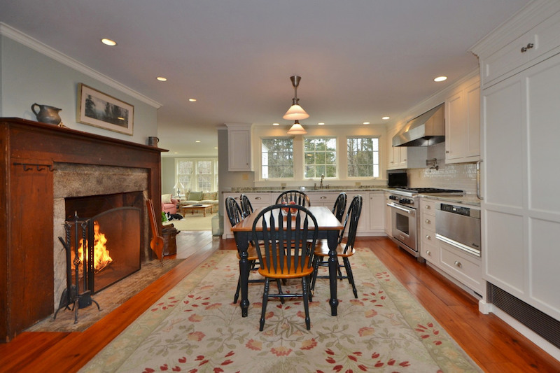A modern kitchen with a farmhouse table and chairs and an original 17th century fireplace.
