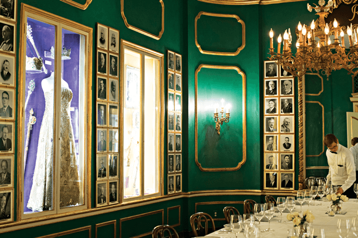 The Green Room at Antoine's Room lined with photographs of past Mardi Gras Queens.