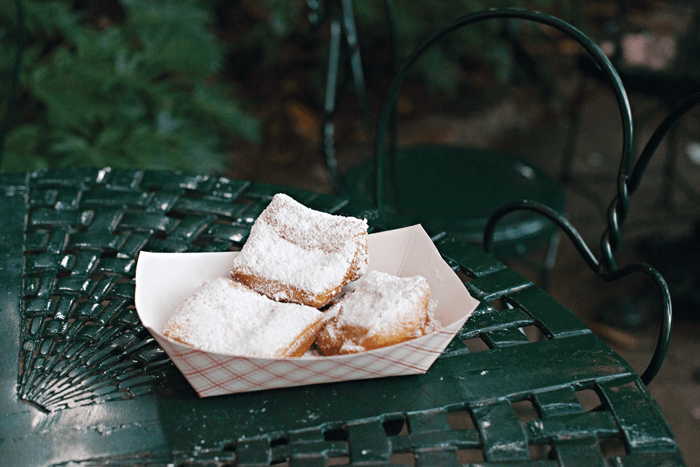 Three freshly sugar-dusted beignets displayed on an ornate, green metal chair.