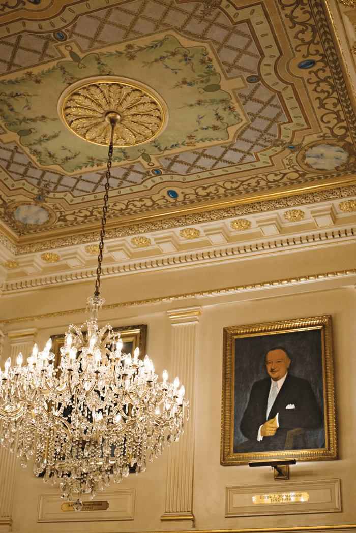 Crystal chandelier hanging from an ornate ceiling with a photograph of the hotel's founder, Antonio Montelone on the wall.