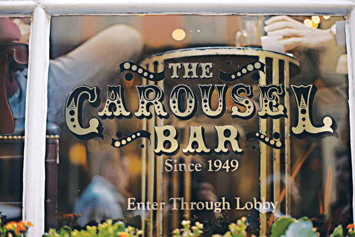 The signage for The Carousel Bar on the front window and a view of the people inside the rotating bar.