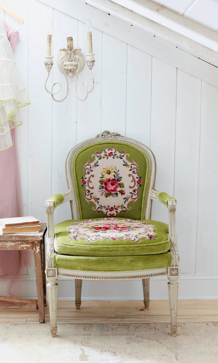 White vertical shiplap walls, stripped floors, ornate green needlepoint covered chair and a rustic wall sconce.