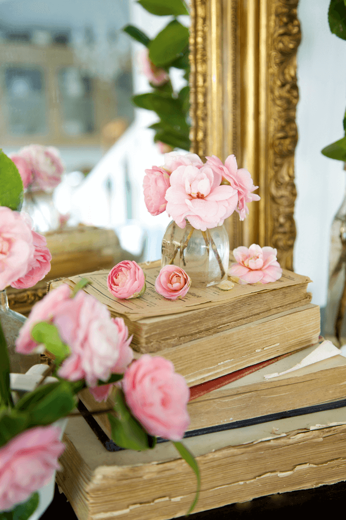 Stack of vintage books topped with pink peonies reflected in ornate gold-trimmed mirror.
