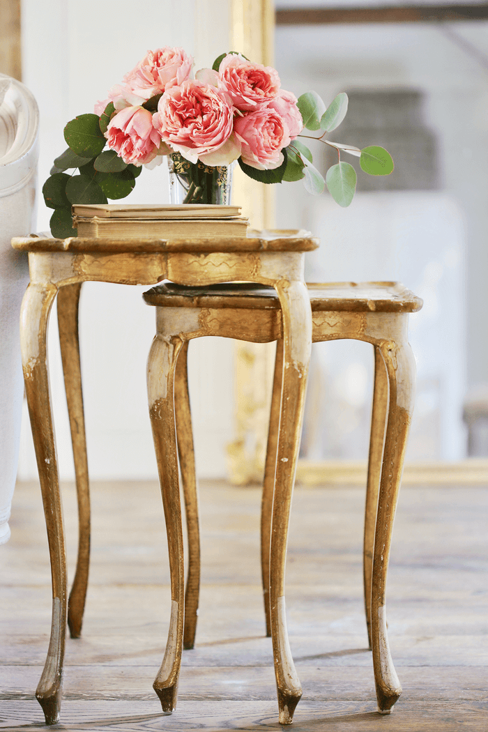 Vintage stacking console tables with a rustic gold finish topped with vintage books and fresh pink peonies.