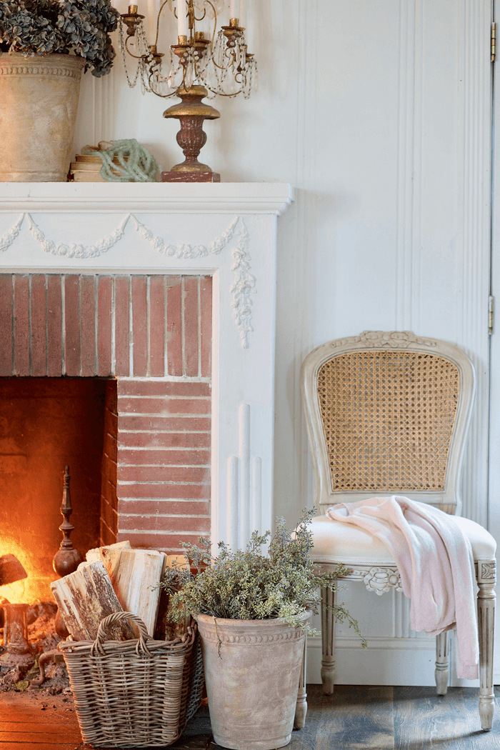 Fire lit in a brick fireplace. Fresh firewood in a basket in front of the fire situated next to a clay pot filled with greenery and a restored chair. Bronze candleabra with white candles on the mantle over the fireplace.
