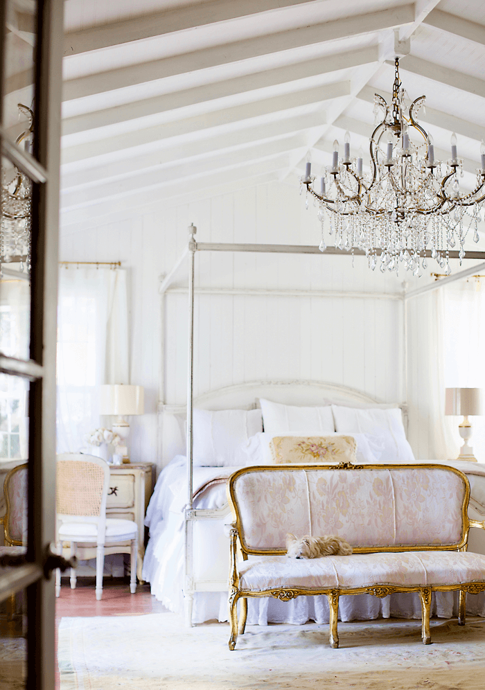White four-poster bed sitting under a vaulted, exposed beam ceiling. Crystal chandelier hanging over the bed and gold rimmed bench at the end of the bed with a small, white dog curled up and asleep on it.
