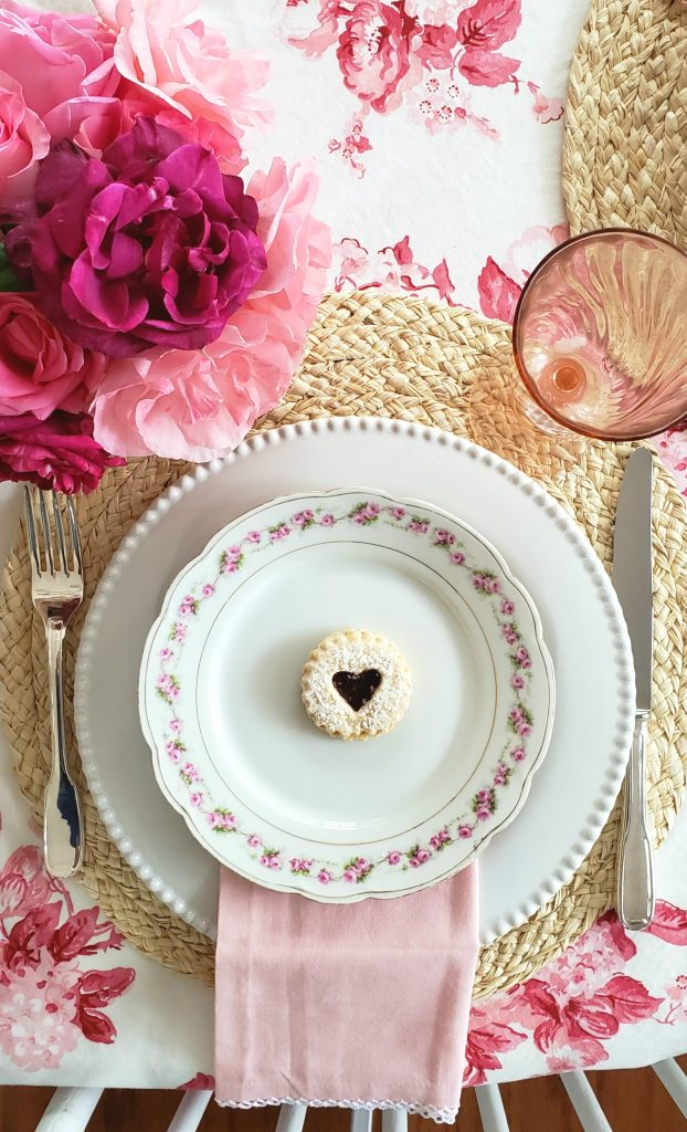 heart cookie on a chintz plate for a pink and red galentines tablescape