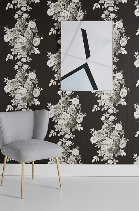 Bold black and gray floral wallpaper , framed wall artwork and a gray armchair