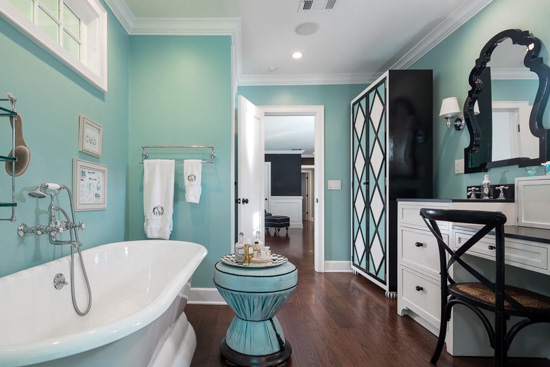 Blue bathroom with black and white accented tub and vanity.