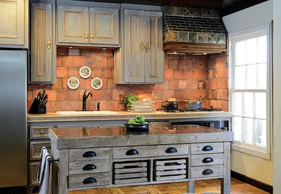 Old world kitchen with terra-cotta tile backsplash and antique island