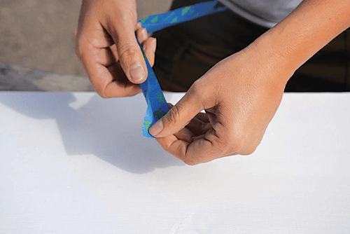 Hands holding painters tape over a white surface.