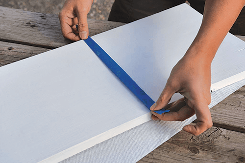 Hands placing painters tape in the center of a white tray.
