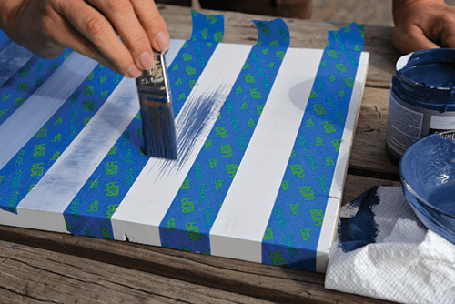 Hand painting light blue in between pre-taped strips of tape.