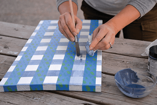 Hands painting into a gingham pattern with freshly placed tape in the opposite direction.