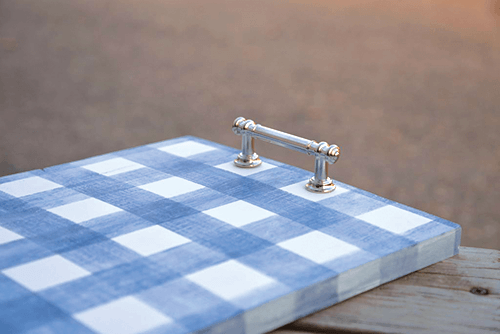 Finished tray with a blue gingham pattern and affixed silver handle to make it into a serving tray.