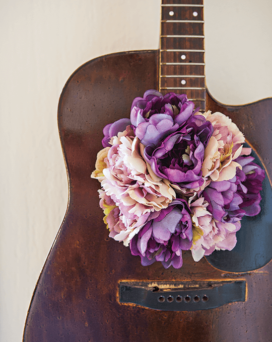 Vintage guitar decorated with purple flowers