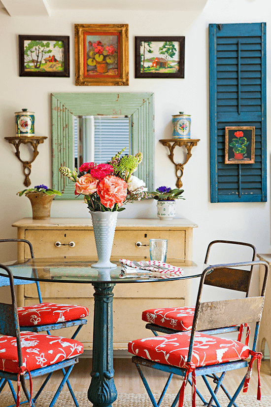 vintage patio set used inside as a dining table. flea market art hangs on the walls