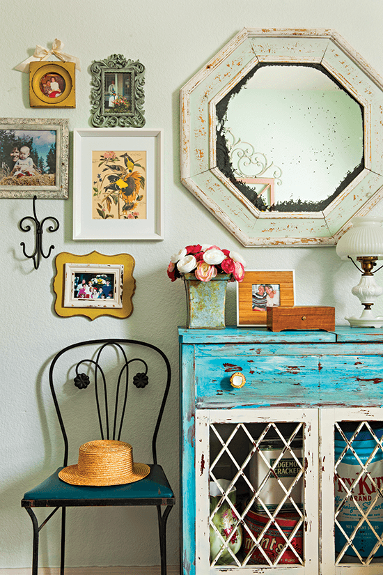 colorful vintage cottage corner with a yard sale find dresser, given a new life and placed as a focal point under a statement mirror and framed family photos on the wall.