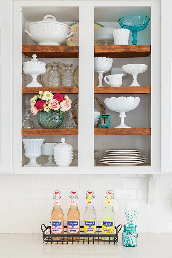 Shaker cabinets with glass panels filled decoratively with fresh flowers and milk glass.