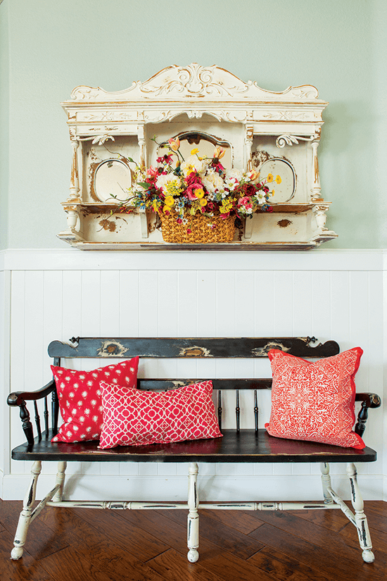 Found and repurposed vintage bench in an entryway, decorated with bright red pillows.