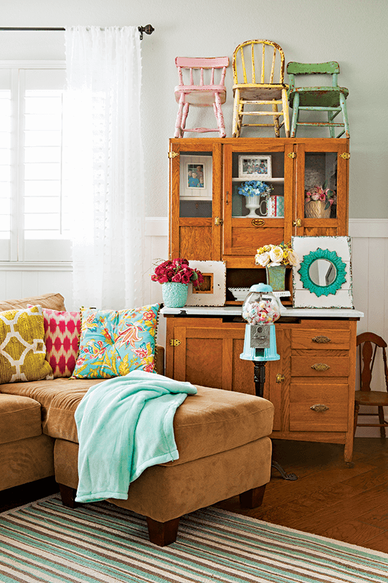 Tan microsuede sectional, brown wooden antique secretary desk covered with vibrantly colored wooden child chairs and featuring an heirloom bubblegum machine.