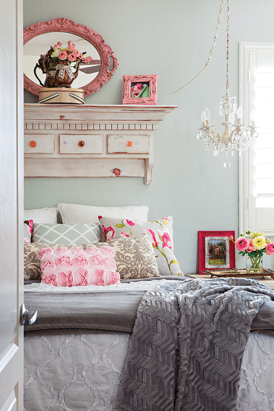 Warm and cozy bed with fuzzy gray throw at the end of the bed. Pink accents and a lovely statement piece above the bed with a small crystal chandelier hanging over the bedside table.