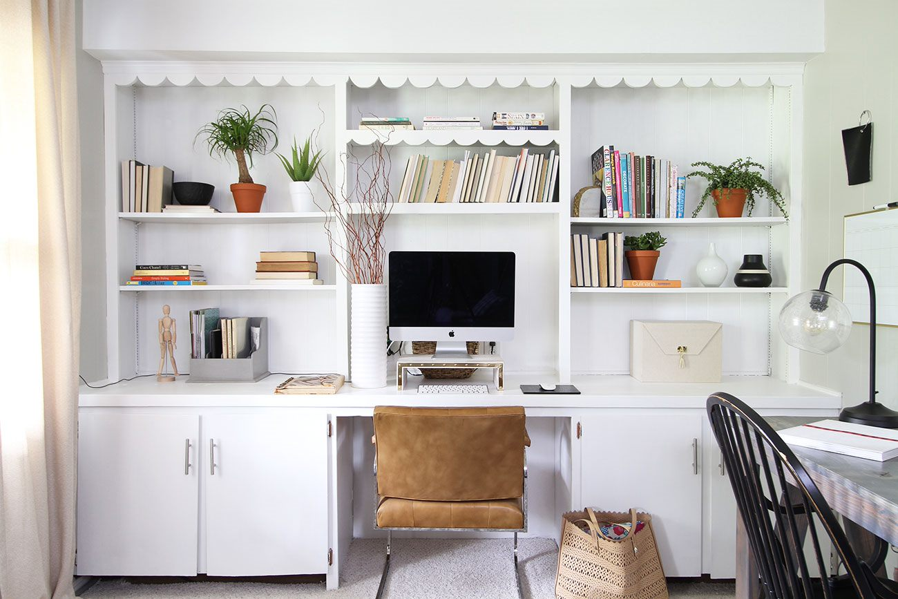 A white office with open shelves that are neatly organized.