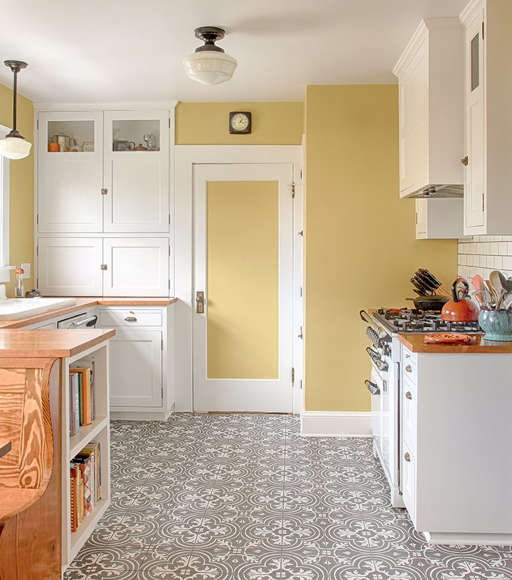 A kitchen with pale yellow walls and a blank-and-white patterned floor.
