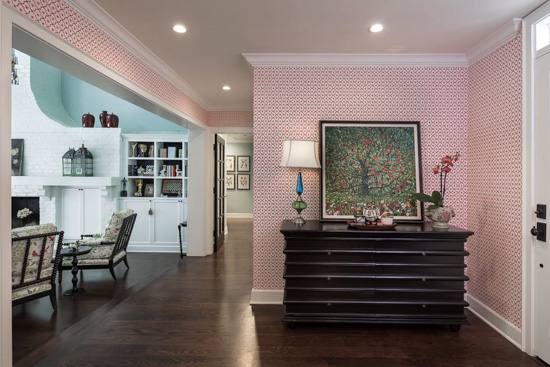 Pink hues cover the walls in this entryway accented with dark wood decor pieces.