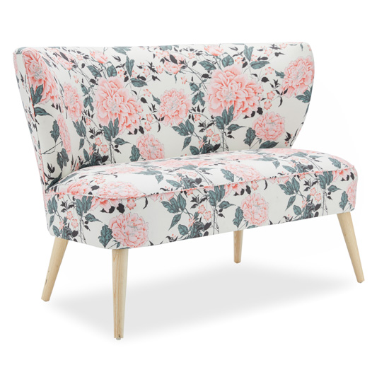 Light colored floral upholstered bench with light wooden legs.
