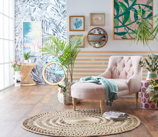 Jute round rug with a blush chaise lounge. Colorful and funky background walls with wallpaper as well as large art pieces, house plant and ceramics decorate the floor around the seating area.