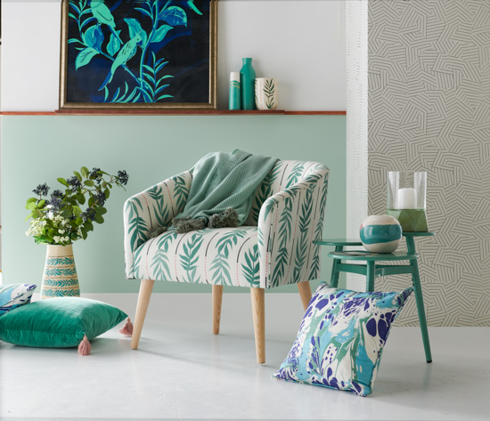 Mint green hues in this seating vignette. Large wall art, ceramic vases, cozy armchair, side table and throw pillows.