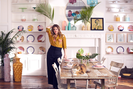 Drew Barrymore standing in a dining room setting. She's next to a rustic looking table with a tabby cat laying on top of it and her new collection is used as decor in the entire scene.