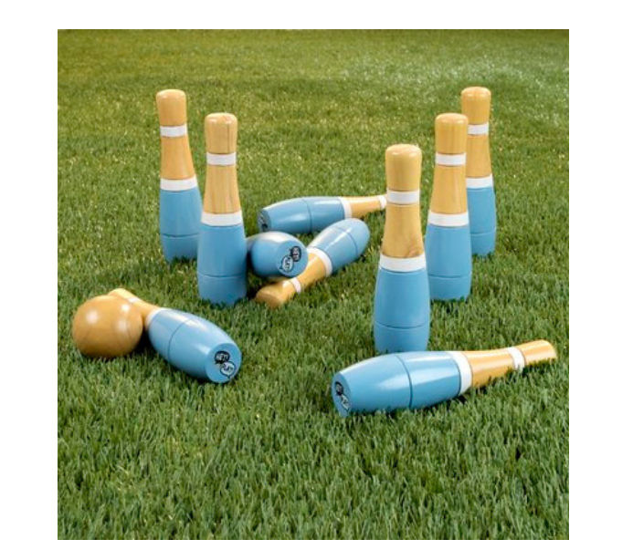Green grass and wooden and turquoise lawn bowling pins and ball
