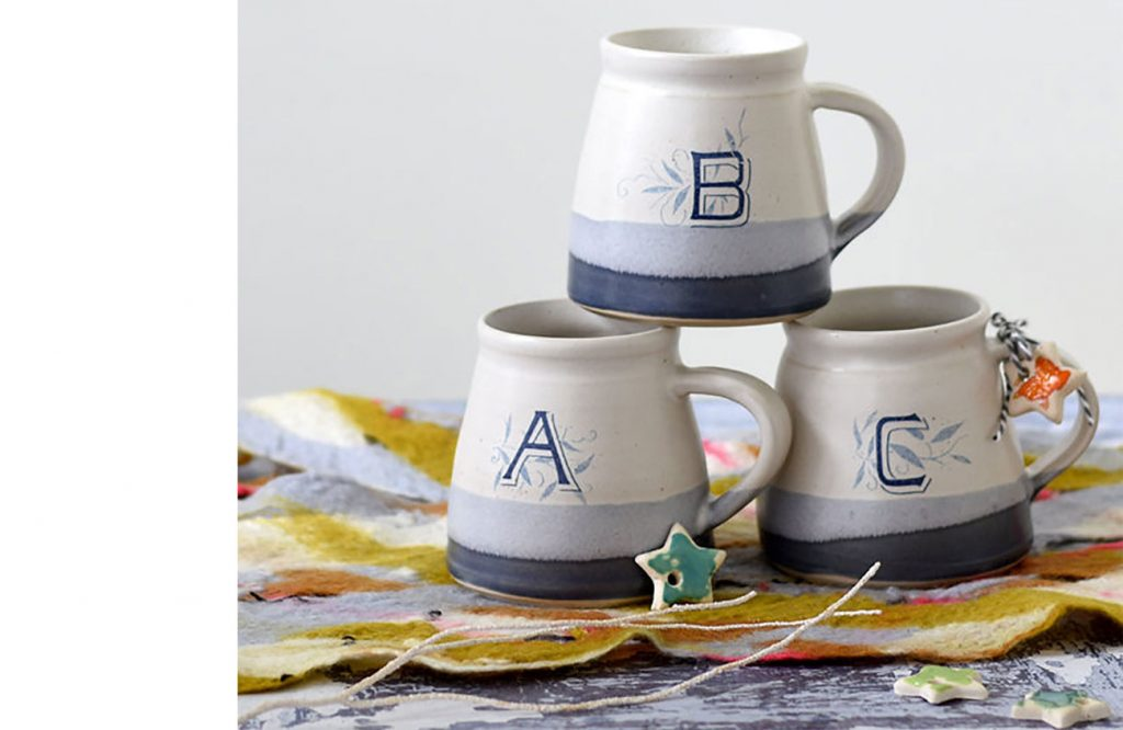 Stack of handmade ceramic monogrammed mugs with letters A, B , and C