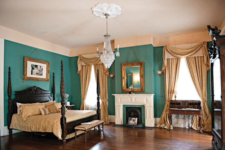 antique four-poster bed and crystal chandelier in a bedroom at Degas House
