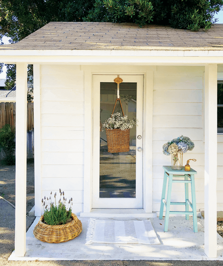 Front view of the she shed welcoming you in with shiplap exterior walls and fresh flowers.