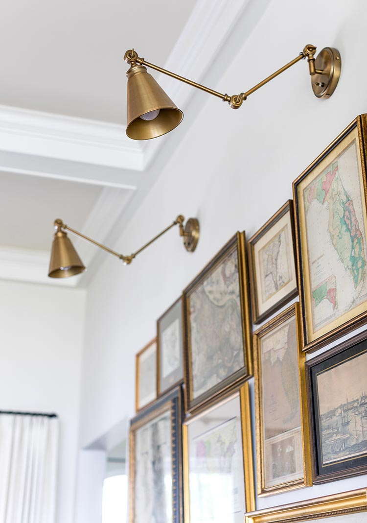 A gallery wall of vintage maps with brass wall sconces