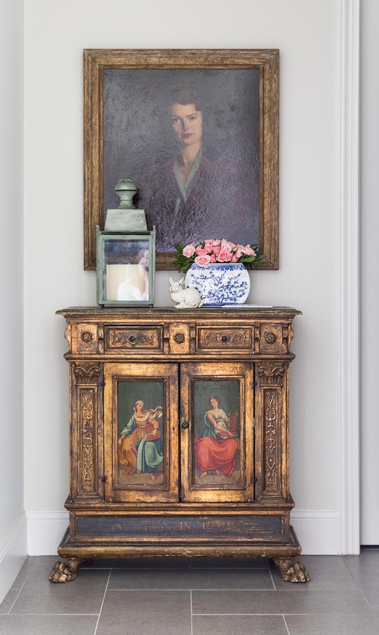 A vintage portrait hanging over a gold cabinet